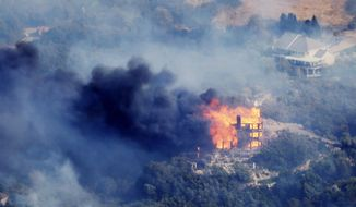 A home burns due to a wildfire at Weber Canyon, Tuesday, Sept. 5, 2017,  in Uintah County, Utah.  At least one home went up in smoke and more than 1,000 people were evacuated as high winds fed the flames that started in a canyon north of Salt Lake City. (Ravell Call/The Deseret News via AP)