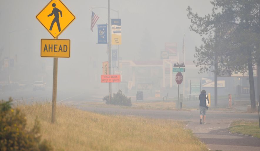 CORRECTS DATE TO SEPT. 1, 2017 - In an Sept. 1, 2017 photo, smoke from the Rice Ridge Fire blankets the town of Seeley Lake, Mont. The lingering wildfire season and endless smoke has affected the Seeley Lake to such a degree that Missoula County health officials urged people to leave to escape the pollution weeks before Tuesday's order to evacuate part of the town due to the encroaching fire. The air quality in Seeley Lake had hourly pollution readings classified as hazardous in 26 days in August. (Rion Sanders/The Great Falls Tribune via AP)