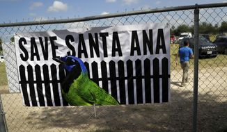In this Aug. 12, 2017, photo, a man walks past a sign in support of Santa Ana National Wildlife Refuge, home to 400-plus species of birds and several endangered wildcats, at a rally in Mission, Texas. The U.S. government carefully designed a path of least resistance to building a border wall in Texas, picking the wildlife refuge and other places it already owns or controls to quickly begin construction. All it needed was Congress to approve the money. (AP Photo/Eric Gay)