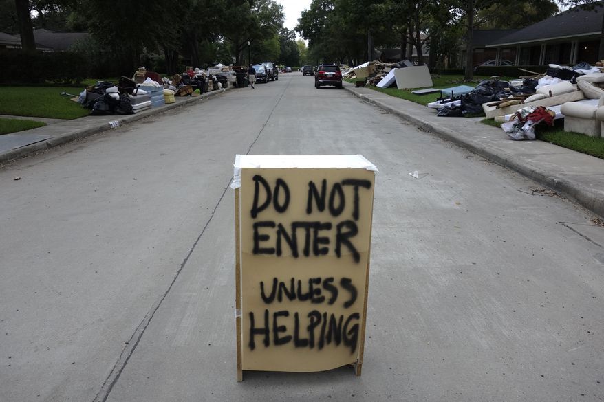 """In this Monday, Sept. 4, 2017 photo, a """"Do Not Enter"""" sign is placed on Tartan Lane, a residential street in Houston. More than a week after Harvey swamped the greater Houston area, the metropolis is divided into two cities: one still covered with water and flood debris, the other largely unblemished by the storm. (AP Photo/Brian Melley)"""