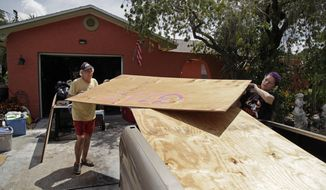 Stan Kreuter, 71, left, and his wife Jackie Kreuter, 56, Gulfport, Fla.,, load plywood in front of their home to take to their downtown Gulfport store Tuesday, Sept. 5, 2017, so they can board it up. Jackie Kreuter, along with her mother, husband, sister, daughter, grandson, five dogs and a bird are boarding up their home and business and leaving for Ocala to get out of Hurricane Irma's way. (Lara Cerri/The Tampa Bay Times via AP)