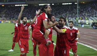 Syria's soccer team celebrates after scoring a goal against Iran during their Round 3 - Group A World Cup qualifier at the Azadi Stadium in Tehran, Iran, Tuesday, Sept. 5, 2017. The match draw 2-2. (AP Photo/Vahid Salemi)