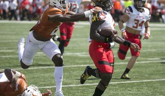 Maryland quarterback Tyrrell Pigrome, front right, eludes Texas' Kris Boyd for a touchdown during second-quarter NCAA college football game action in Austin, Texas, Saturday, Sept. 2, 2017. (Ralph Barrera/Austin American-Statesman via AP)