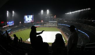 Baseball fans wait out a rain delay before the start of a scheduled a baseball game between Atlanta Braves and Texas Rangers, Tuesday, Sept. 5, 2017, in Atlanta. (AP Photo/John Bazemore)