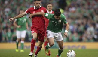 Republic of Ireland's Shane Long, right, and Serbia's Antonio Rukavina in action during the 2018 FIFA World Cup Qualifying, Group D match at the Aviva Stadium in Dublin, Ireland, Tuesday Sept. 5, 2017. (Niall Carson/PA via AP)