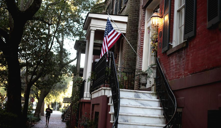 ADVANCE FOR USE FRIDAY, SEPT. 8, 2017 AND THEREAFTER-In this Feb. 21, 2011 photo, a U.S. flag decorates the front door of a home in the historic district of Savannah, Ga. Lured by the city's time-capsule collection of antebellum homes and manicured public squares, tourists spent an estimated $2.8 billion here in 2016. Beyond the picturesque 2 square miles of the downtown historic district, the scenery gives way to neighborhoods reeling from poverty. (AP Photo/David Goldman)