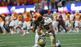 Georgia Tech quarterback TaQuon Marshall (16) kneels on the turf as Tennessee players rush the field after the second over time period of an NCAA college football game Tuesday, Sept. 5, 2017, in Atlanta. Tennessee won 42-41. (AP Photo/John Bazemore)
