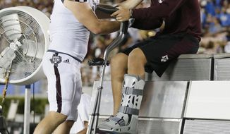 Texas A&M linebacker Cullen Gillaspia, left, checks on Texas A&M quarterback Nick Starkel, right, as he sits on the bench with an injury against UCLA during the second half of an NCAA college football game, Sunday, Sept. 3, 2017, in Pasadena, Calif. (AP Photo/Danny Moloshok)