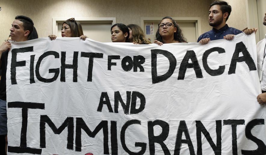 People hold up a banner during an event to protest President Donald Trump's decision to revoke the Deferred Action for Childhood Arrivals program, Tuesday, Sept. 5, 2017, in Las Vegas. President Donald Trump on Tuesday began dismantling the Deferred Action for Childhood Arrivals, or DACA, program, the government program protecting hundreds of thousands of young immigrants who were brought into the country illegally as children. (AP Photo/John Locher)