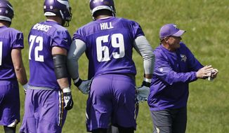 Clancy Barone, Minnesota Vikings tight end coach, gives instructions as offensive linemen Mike Remmers, left, and Rashod Hill listen in during the NFL football team's practice Tuesday, Sept. 5, 2017, in Eden Prairie, Minn. The Minnesota Vikings are going to start the season with a completely remade offensive line. New faces Riley Reiff, Mike Remmers and Pat Elflein will be counted on to improve a unit that was one of the league's worst last season. (AP Photo/Jim Mone)