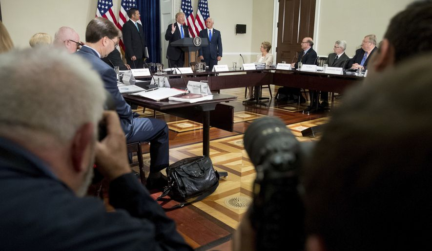 President Donald Trump, accompanied by Vice President Mike Pence, center right, and Kansas Secretary of State Kris Kobach, center left, speaks during the first meeting of the Presidential Advisory Commission on Election Integrity at the Eisenhower Executive Office Building on the White House complex in Washington, Wednesday, July 19, 2017. (AP Photo/Andrew Harnik)