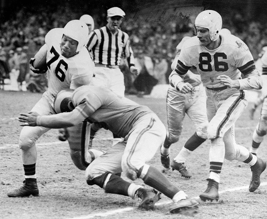 15. 1950 Cleveland Browns: 10-2, NFL Champions - Cleveland fullback Marion Motley (76) picks up 12 yards and a first down in the fourth period of Brown-Los Angeles Rams game for the National Pro Football League championship, at Cleveland, Ohio, Dec. 24, 1950. Rams' halfback Paul Younger tackles Motley as Cleveland halfback Dub Jones (86), running interference for ball carrier, comes up too late to put a block on the tackler. Browns took the title by beating the Rams 30-28 on Lou Groza's field goal in last twenty seconds of play. (AP Photo)