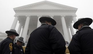 Virginia State Police stand outside the Virginia State Capitol as fog envelopes the area before inaugural ceremonies for Governor-elect Terry McAuliffe in Richmond, Va., Saturday, Jan. 11, 2014. (Associated Press) **FILE**