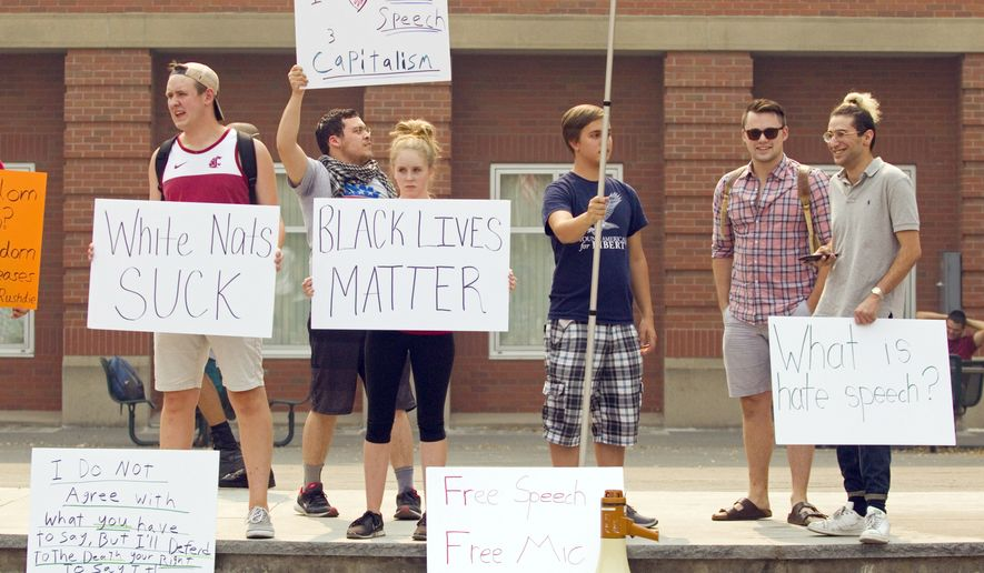 Washington State University College Republicans President Amir Rezamand, right, and his predecessor, James Allsup, second from right, who resigned after attending the Confederate monuments protest in Charlottesville, Va., talk with unidentified students during a small rally for Free Speech organized by the Washington State University chapter of Young Americans For Liberty on Wednesday, Sept. 6, 2017 in Pullman, Wash. (Geoff Crimmins/The Moscow-Pullman Daily News via AP)