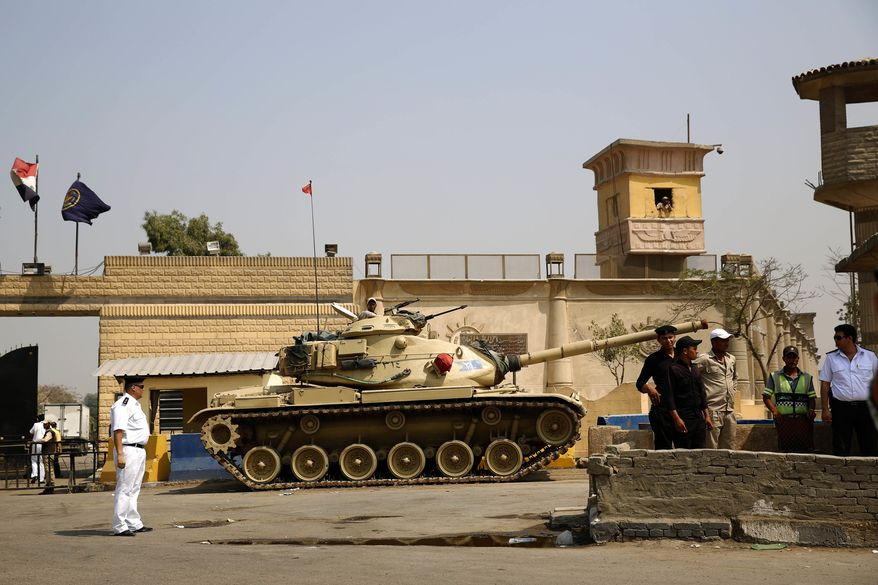 In this Aug. 2, 2015, file photo, Egyptian security forces stand guard outside one of the entrances of Tora prison, in Cairo, Egypt. Human Rights Watch, an international rights group, is alleging systematic torture inside Egyptian police stations and Interior Ministry headquarters where officers act in almost total impunity. In a 63-page study released Wednesday, Aug. 6, 2017,  HRW said President Abdel-Fattah el-Sissi's pursuit of stability comes at any cost.  (AP Photo/Hassan Ammar, File)