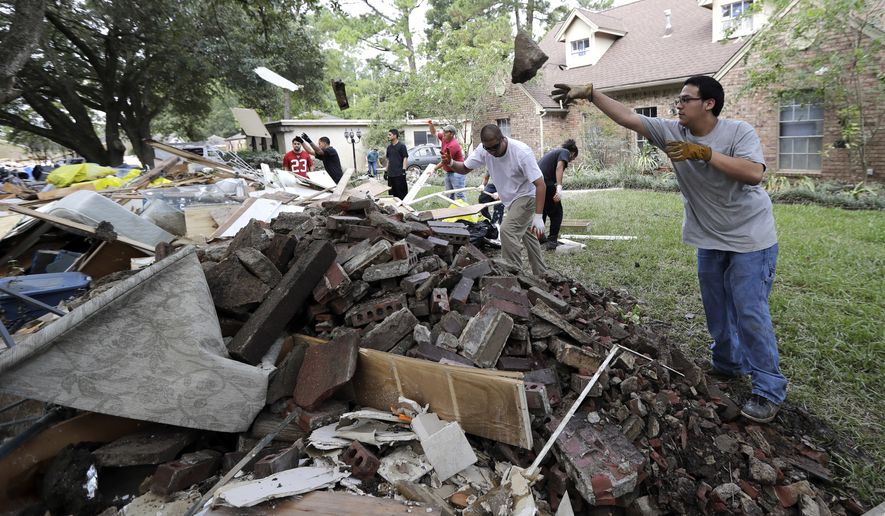 Workers help move debris from a home damaged by floodwaters in the aftermath of Hurricane Harvey on Wednesday, Sept. 6, 2017, in Spring, Texas. (AP Photo/David J. Phillip)