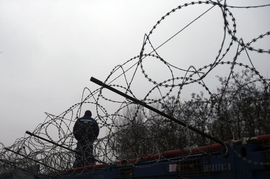 In this file photo dated Wednesday, Feb. 8, 2017, a Hungarian police officer stands guard at Serbia's border with Hungary near a makeshift camp for migrants in Horgos, Serbia.  The European Court of Justice on Wednesday Sept.6, 2017, rejected efforts by Hungary and Slovakia to stay out of a European Union scheme to relocate refugees. (AP Photo/Darko Vojinovic, FILE)