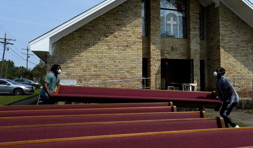 Camron Coleman, left, and Jordan Benoit move a damaged pew out of Magnolia Missionary Baptist Church on Pine Street in the north end of Beaumont, Texas, Wednesday, Sept. 6, 2017. (Ryan Pelham/The Beaumont Enterprise via AP)