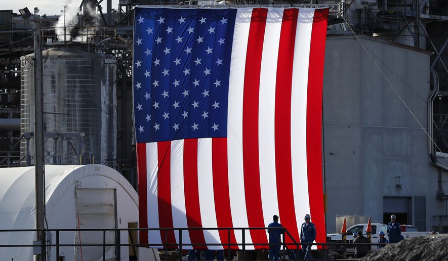 Workers stand in front of a flag on the side of the Andeavor Mandan Refinery before the arrival President Donald Trump, Wednesday, Sept. 6, 2017, in Mandan, N.D. (AP Photo/Charlie Neibergall)