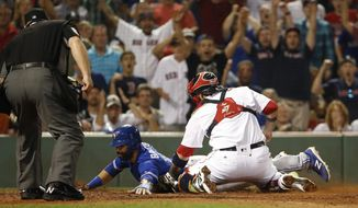 Boston Red Sox catcher Sandy Leon tags out Toronto Blue Jays' Jose Bautista trying to score on a fly ball during the 11th inning of a baseball game at Fenway Park in Boston, Tuesday, Sept. 5, 2017. (AP Photo/Winslow Townson)