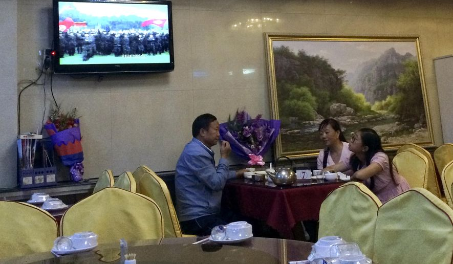 In this Monday, Sept. 4, 2017 photo, Chinese people watch a TV showing a North Korean propaganda program as they dine at a North Korean restaurant in Dandong, northeastern China's Liaoning province. Rising international tensions over Pyongyang's missile launches and nuclear tests seem a distant concern in the Chinese border city of Dandong, where trucks rumble across the bridge to North Korea and people stroll the promenade beside the Yalu River within sight of North Korean border guards. (AP Photo/Helene Franchineau)