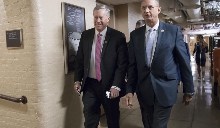 Rep. Mark Meadows, R-N.C., left, chairman of the conservative House Freedom Caucus, and Rep. Doug Collins, R-Ga., right, walk to a meeting of House Republicans as work in Congress resumes following the August recess, at the Capitol in Washington, Wednesday, Sept. 6, 2017. Meadows is opposed to suggestions by GOP leaders to connect the urgent Harvey aid bill to increasing the U.S. debt limit. (AP Photo/J. Scott Applewhite)