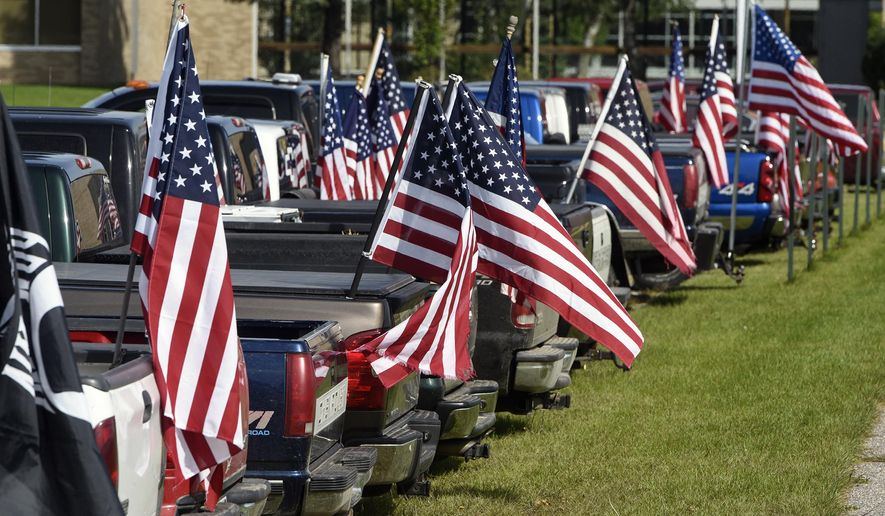 Dozens of American flags fly from a row of student vehicles Wednesday, Sept. 6, 2017, in the parking lot of Rocori High School in Cold Spring, Minn. Students at a central Minnesota high school are flying American flags on their pickup trucks to protest a recent ban. Rocori High School in Cold Spring has changed the student handbook to ban all flags and banners on vehicles in the school parking lot.(Dave Schwarz/St. Cloud Times via AP)