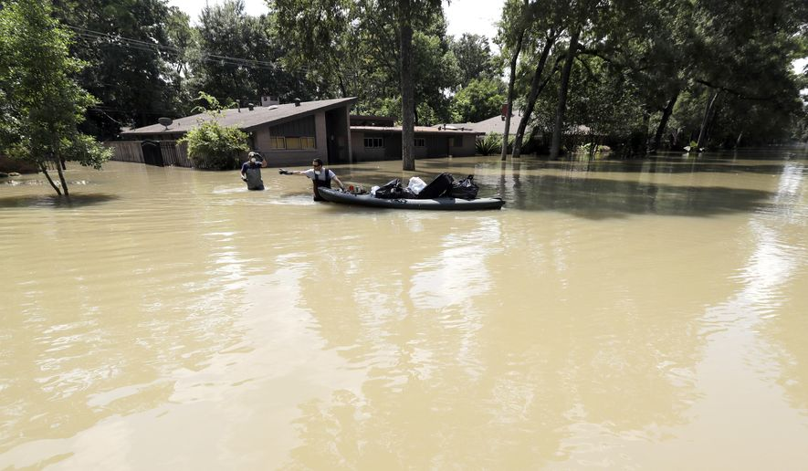 Gaston Kirby, right, and Juan Minutella leave Kirby's flooded home in the aftermath of Hurricane Harvey, Monday, Sept. 4, 2017, near the Addicks and Barker Reservoirs, in Houston. (AP Photo/David J. Phillip)