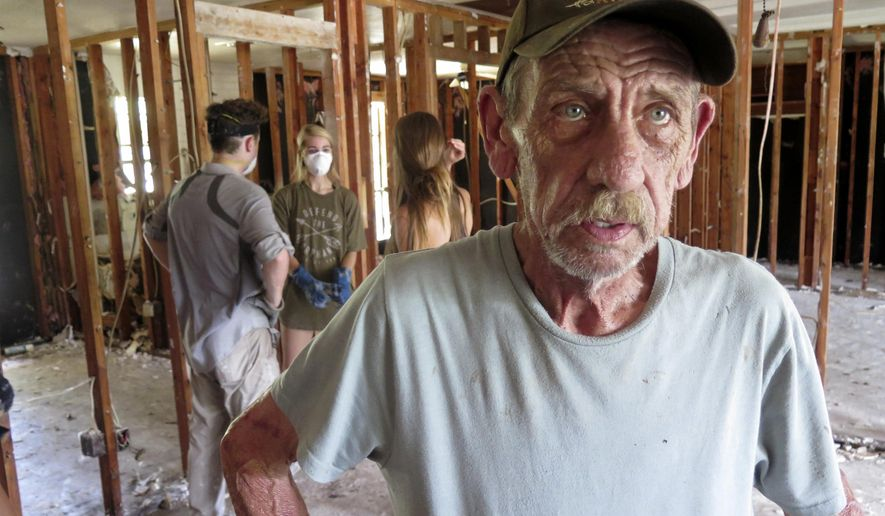In this Monday, Sept. 4, 2017, photo, Bob Janak, of Magnolia, Texas, stands inside his home that was damaged by floodwaters caused by Hurricane Harvey. After riding out the storm in a Motel 8 and waiting an agonizing week for the waist-high waters to recede, Janak returned to his wrecked home to find volunteers who took it upon themselves to help clean out the modest ranch house. (AP Photo/Robin McDowell)
