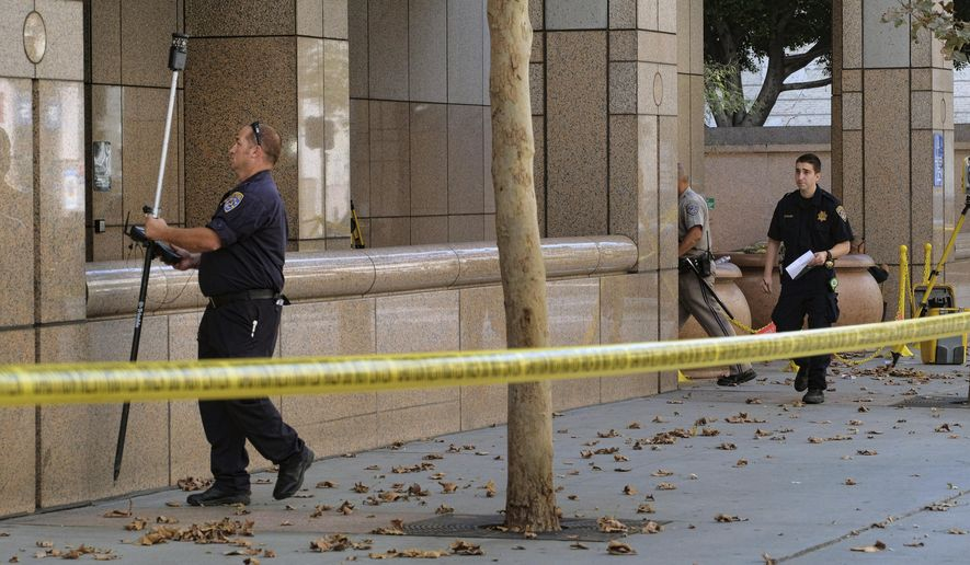 "Authorities investigate an officer involved shooting at The Ronald Reagan State Office Building in downtown Los Angeles on Wednesday, Sept. 6, 2017. A man with a bag over his hands followed an employee into the building took ""an aggressive shooting stance"" and ordered workers to the ground before an officer fatally shot him. (AP Photo/Richard Vogel)"
