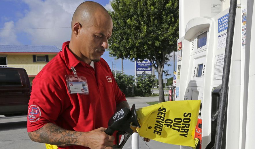 Gas station employee Albert Fernandez covers a pump after running out of gas as the demand for gas has increased due to Hurricane Irma, Wednesday, Sept. 6, 2017, in Key Largo, Fla.  Irma roared into the Caribbean with record force early Wednesday, its winds shaking homes and flooding buildings on a chain of small islands along a path toward Puerto Rico, the Dominican Republic, Haiti, Cuba and likely Florida by the weekend. (AP Photo/Alan Diaz)