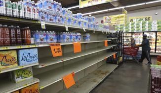 A shelf normally containing packaged water sits empty at a Piggly Wiggly store Tueday, Sept. 5, 2017, in Panama City, Fla. Store managers informed shoppers that more water will be delivered on Sept.6 in the morning a residents prepare for Hurricane Irma. (Patti Blake/News Herald via AP)