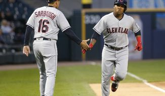 Cleveland Indians third base coach Mike Sarbaugh, left, greets Jose Ramirez at third after Ramirez's home run off Chicago White Sox's David Holmberg during the first inning of a baseball game Tuesday, Sept. 5, 2017, in Chicago. (AP Photo/Charles Rex Arbogast)