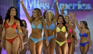 Contestants greet onstage in the swimsuit completion during the first night of Miss America 2018 preliminaries in Atlantic City, N.J., Wednesday, Sept. 6, 2017. In June 2018, Miss America pageant organizers announced the contest will drop its swimsuit and evening gown competitions moving forward. (Tom Gralish/The Philadelphia Inquirer via AP) **FILE**