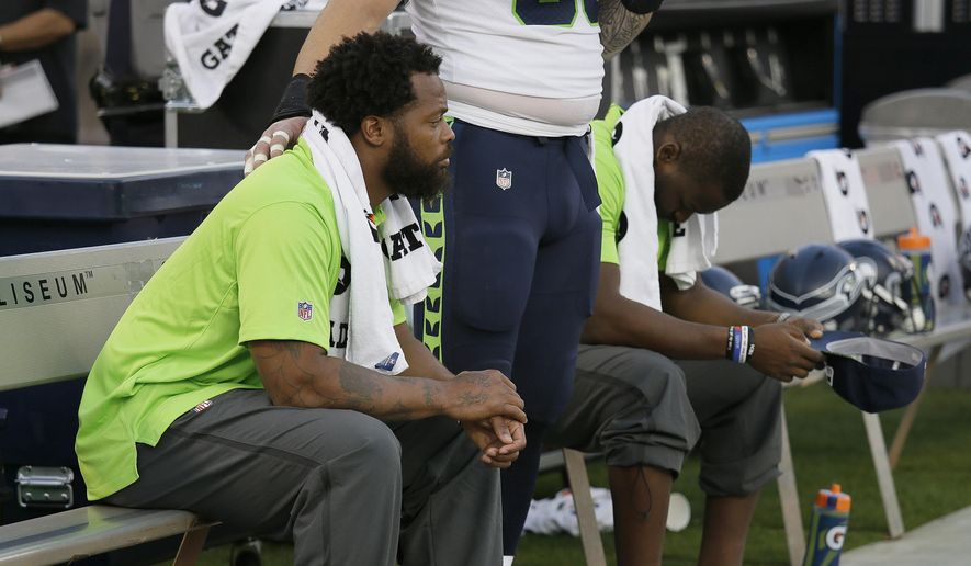 FILE - This Thursday, Aug. 31, 2017 file photo Seattle Seahawks defensive end Michael Bennett, left, sits during the playing of the national anthem next to Justin Britt, center, and another teammate before an NFL preseason football game between the Raiders and the Seattle Seahawks in Oakland, Calif. Bennett is accusing Las Vegas police of racially motivated excessive force when he says he was detained at gunpoint on Aug. 27, 2017, handcuffed and later released without charges following a report that gunshots were heard at a casino hotel. (AP Photo/Eric Risberg,File) **FILE**