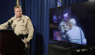 Las Vegas police Undersheriff Kevin McMahill watches body camera footage during a press conference on accusations by Seattle Seahawks player Michael Bennett, Wednesday, Sept. 6, 2017, in Las Vegas. Bennett has accused Las Vegas police of racially motivated excessive force in a Twitter posting saying he was threatened at gunpoint following a report of gunshots at an after-hours club at a casino-hotel. (AP Photo/John Locher)