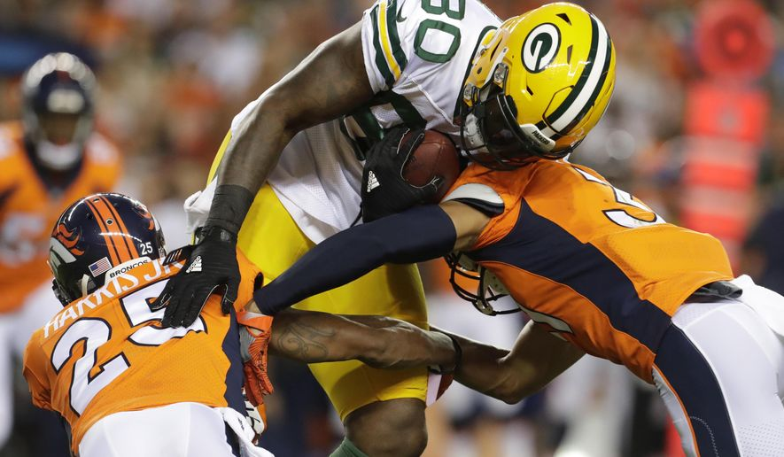 """File- This Aug. 26, 2017, file photo shows Green Bay Packers tight end Martellus Bennett (80) being hit by Denver Broncos cornerback Chris Harris (25) during the first half of an NFL preseason football game, in Denver.   So many new veterans for the Green Bay Packers. At their core, the Packers still build through the draft. But general manager Ted Thompson has been more active than usual this season in signing veteran free agents. """"Well, I think you have to realize that any time you acquire a player, whether it's through the draft, free agency, regardless of the time of year, it's a process. It's a process that's always going on,"""" coach Mike McCarthy said before practice Wednesday, Sept. 6, 2017. (AP Photo/Joe Mahoney, File)"""
