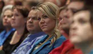 FILE - In this Nov. 30, 2012, file photo, Elissa Wall attends a community meeting regarding the United Effort Plan (UEP) trust, in Colorado City, Ariz. Wall who was married to her cousin at age 14 in a ceremony overseen by polygamous sect leader Warren Jeffs has won a $16 million lawsuit against the group. Wall's lawyer said Wednesday, Sept. 6, 2017, that the decision lets attorneys investigate the secretive group's bank accounts and property held in states all over the U.S.(Trent Nelson/The Salt Lake Tribune via AP, File)