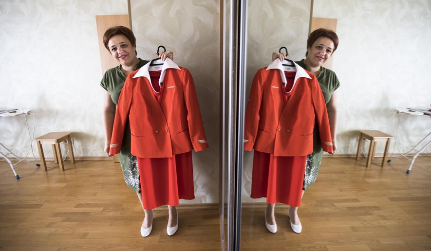 FILE - In this file photo taken on Thursday, Aug. 3, 2017, Aeroflot flight attendant Yevgeniya Magurina shows her uniform during an interview with the Associated Press in Lobnya, outside Moscow, Russia.  A Moscow court has ruled in favor of Magurina who claimed that Russia's flagship airline Aeroflot discriminated against her based on appearance.. (AP Photo/Alexander Zemlianichenko, FILE)