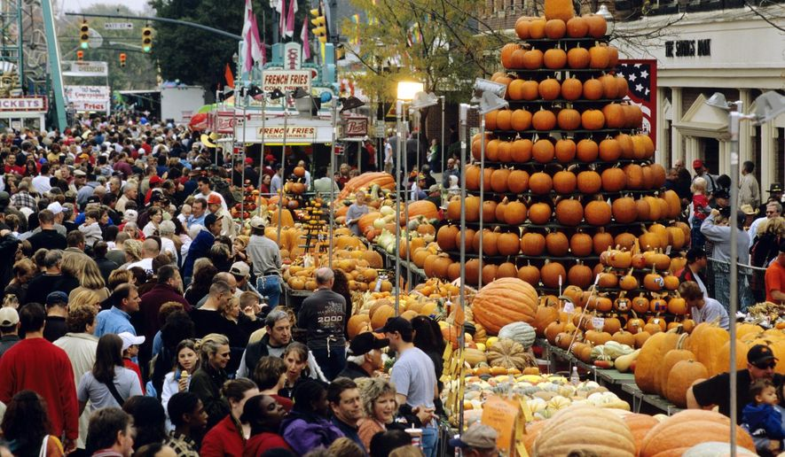 This undated photo provided by TourismOhio shows a display of pumpkins shaped like a tree amid crowds at the Circleville Pumpkin Show in Circleville, Ohio. The small town of just 12,000 people south of Columbus attracts tens of thousands of visitors to its free pumpkin festival each October, this year scheduled for Oct. 18-21. (TourismOhio via AP)