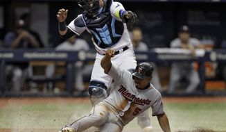 Minnesota Twins' Eduardo Escobar (5) scores ahead of the tag by Tampa Bay Rays catcher Jesus Sucre on a sacrifice fly by Robbie Grossman during the ninth inning of a baseball game Wednesday, Sept. 6, 2017, in St. Petersburg, Fla. (AP Photo/Chris O'Meara)