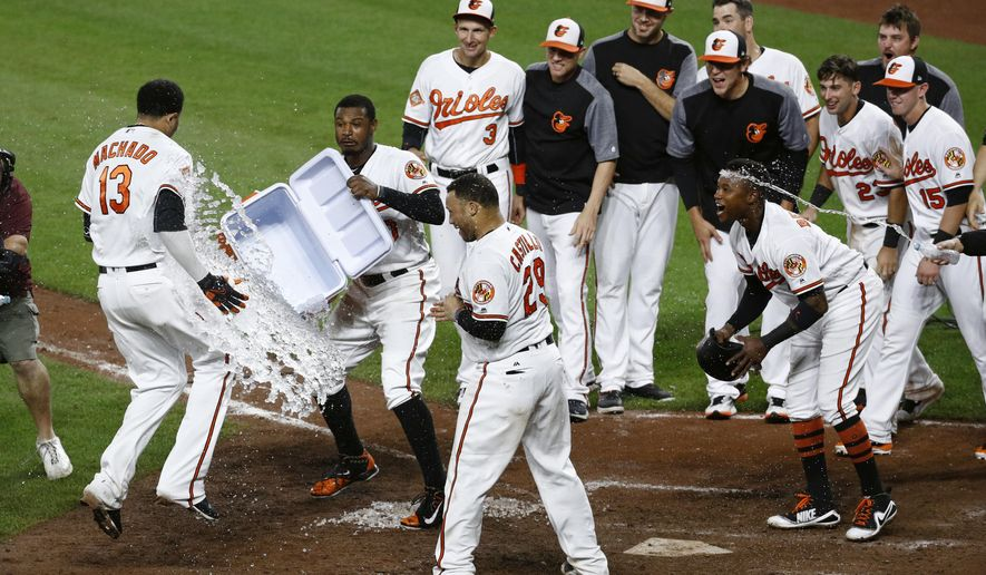 Baltimore Orioles' Adam Jones, second from left, throws ice water at teammate Manny Machado (13) after Machado hit a two-run home run in the ninth inning of a baseball game against the New York Yankees in Baltimore, Wednesday, Sept. 6, 2017. Baltimore won 7-6. (AP Photo/Patrick Semansky)