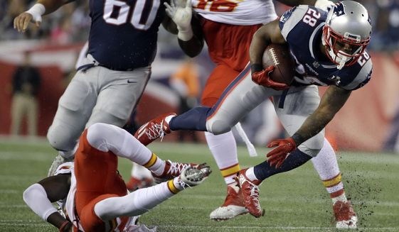 Kansas City Chiefs safety Ron Parker, bottom left, trips up New England Patriots running back James White (28) as he carries the ball during the first half of an NFL football game, Thursday, Sept. 7, 2017, in Foxborough, Mass. (AP Photo/Steven Senne)