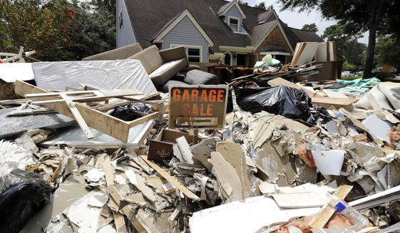 In this Sunday, Sept. 3, 2017, file photo, a garage sale sign stands in a pile of debris damaged by floodwaters in the aftermath of Hurricane Harvey in Spring, Texas. Doing an inventory of all of your possessions while your home is safe and sound makes it easier to file an insurance claim after a disaster such as Hurricane Harvey. (AP Photo/David J. Phillip, File)