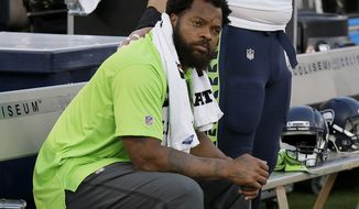 FILE - In this Aug. 31, 2017, file photo, Seattle Seahawks defensive end Michael Bennett sits during the playing of the national anthem before an NFL preseason football game between the Raiders and Seahawks in Oakland, Calif. Packers tight end Martellus Bennett plans to give his older brother, Seattle Seahawks defensive end Michael Bennett, a hug when he sees him this weekend. Recent events off the football field make the high-profile season opener on Sunday between Green Bay and Seattle seem trivial by comparison. (AP Photo/Eric Risberg, File)