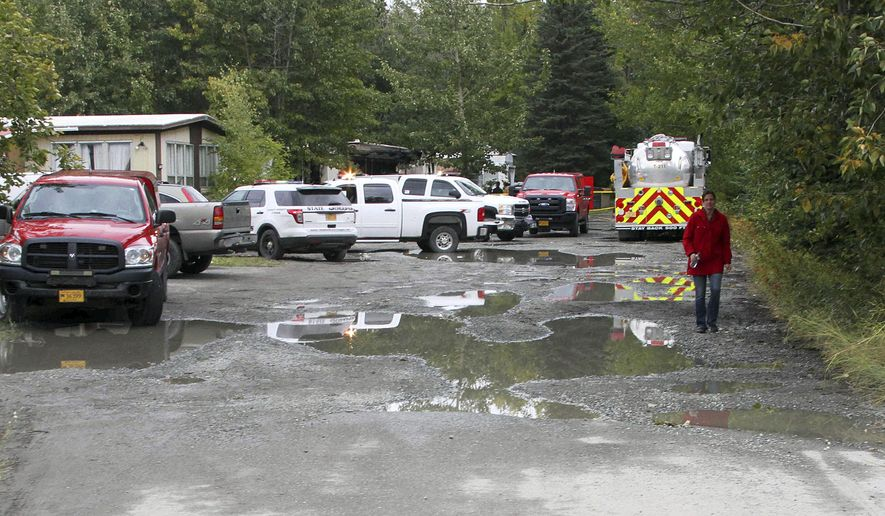The charred remains of a trailer home where five children died in a fire are seen beyond police and fire vehicles in The Butte, Alaska, a suburb of Anchorage, on Thursday, Sept. 7, 2017. Officials believe the victims were five girls, all between the ages of 3 and 12. (AP Photo/Mark Thiessen)