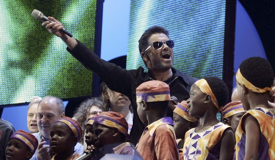 """FILE - In this Saturday, July 2, 2005 file photo, British singer George Michael accompanied by other musicians and children from Africa gestures to the crowds during the Live 8 concert in Hyde Park, London. A new single by George Michael has been released, eight month after the music star's death. """"Fantasy,"""" first recorded in the late 1980s, has been reworked by funk-master Nile Rodgers and received its first radio airplay on Thursday, Sept. 7, 2017. Rodgers tweeted that he felt """"emotional ambiguity"""" about the song, which evoked """"tears, uncertainty, happiness and love."""" (AP Photo/Lefteris Pitarakis, File)"""