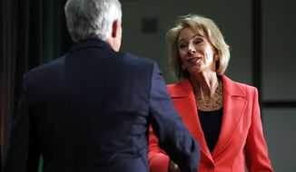 "Henry Butler, dean of the Antonin Scalia Law School at George Mason University, greeted Betsy DeVos on Thursday before the secretary of education announced ""The era of 'rule by letter' is over."" (Associated Press)"