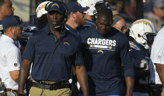 FILE - In this Aug. 26, 2017, file photo, Los Angeles Chargers head coach Anthony Lynn, front left, walks with Los Angeles Chargers tight end Antonio Gates, right, during the first half of a preseason NFL football game against the Los Angeles Rams in Los Angeles. The  Chargers' game against the Denver Broncos on Monday, Sept. 11, 2017, presents landmarks on the football field, along the sidelines and in the broadcast booth. (AP Photo/Mark J. Terrill, File)