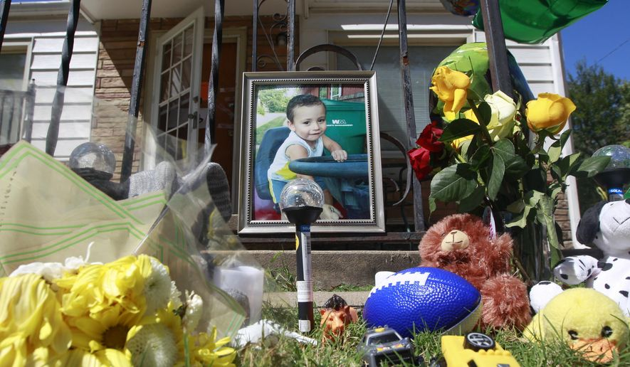 A memorial to three-year-old Evan Brewer sits in front of a home in Wichita, Kan., Wednesday, Sept. 6, 2017. A boy, whose body was found encased in concrete in a Wichita rental home, is believed to be the son of a woman named in an order seeking to protect him from abuse, police said Tuesday. Wichita police Lt. Jeff Gilmore told reporters that the body found Saturday in the rental home is likely that of Brewer, though authorities are awaiting DNA results for final confirmation. (Fernando Salazar/The Wichita Eagle via AP)